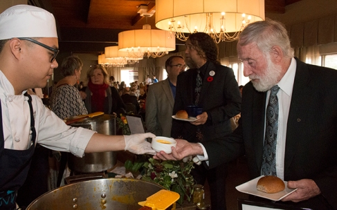 Second year DC culinary management student, Shiwei Yin, or 'Oliver' as he is known to his friends, serves Bowmanville food bank volunteer Hugh Allison a bowl of buttercup squash and carrot soup from Bistro '67 at the Empty Bowls event at the Oshawa Golf and Curling Club. Phot by Barbara Howe