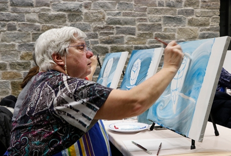 Gloria Nago tries her hand at painting at the Bistro '67. Photo by Barbara Howe